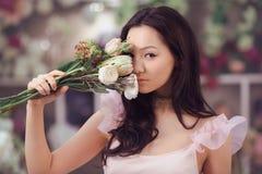 Florista asiático bonito da mulher no vestido cor-de-rosa com o ramalhete das flores nas mãos na loja de flor Foto de Stock Royalty Free