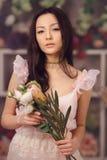 Florista asiático bonito da mulher no vestido cor-de-rosa com o ramalhete das flores nas mãos na loja de flor Imagens de Stock Royalty Free