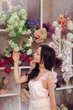 Florista asiático bonito da mulher no vestido cor-de-rosa na loja de flor Fotos de Stock Royalty Free