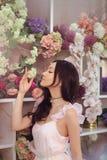 Florista asiático bonito da mulher no vestido cor-de-rosa na loja de flor Fotografia de Stock Royalty Free