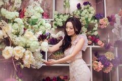 Florista asiático bonito da mulher no vestido cor-de-rosa na loja de flor Imagens de Stock
