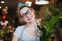 Florista bonito alegre da jovem mulher nos vidros no florista Imagem de Stock Royalty Free