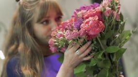 Florista bonito da jovem mulher que aspira um ramalhete bonito das flores Menina bonita que guarda um grupo de flores na flor vídeos de arquivo