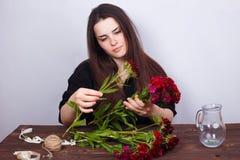 Florista bonito novo da mulher que faz o ramalhete dos cravos flor imagens de stock royalty free