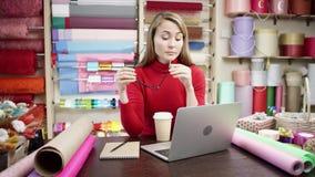 Florista cansado de sexo femenino que habla en el teléfono móvil mientras que usando el ordenador portátil en la floristería, ord almacen de video