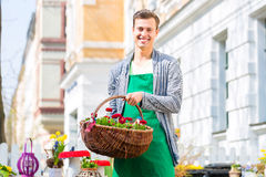 Florista com a cesta da flor na venda da loja Imagens de Stock
