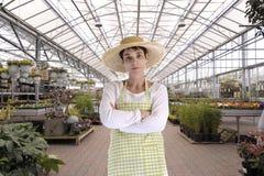 Florista com o chapéu na estufa Fotografia de Stock Royalty Free