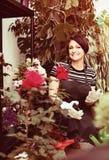 Florista con las herramientas en la tienda que cultiva un huerto Imágenes de archivo libres de regalías