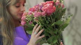 Florista da jovem mulher que aspira um ramalhete bonito das flores Menina bonita que guarda um grupo de flores no florista video estoque