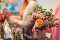 Florista da oficina, fazendo ramalhetes e arranjos de flor Mulher que recolhe um ramalhete das rosas Foco macio Imagem de Stock