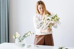 Florista de la muchacha que monta un ramo imagen de archivo
