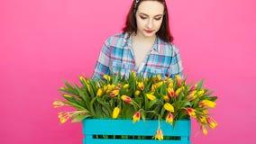 Florista de sexo femenino joven con la caja grande de tulipanes amarillos almacen de metraje de vídeo