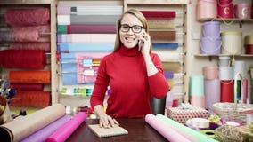 Florista de sexo femenino que habla en el teléfono móvil mientras que usa el ordenador portátil en la floristería, orden del cont almacen de metraje de vídeo