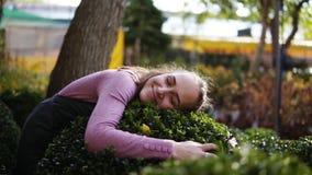 Florista de sexo femenino sonriente en boj verde del abarcamiento del delantal en el invernadero, sonrisa y mirada en la cámara F metrajes