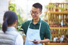 Florista de sexo masculino Talking a su cliente en la tienda Imagen de archivo libre de regalías