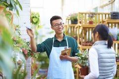 Florista de sexo masculino Talking a su cliente en la tienda Imágenes de archivo libres de regalías