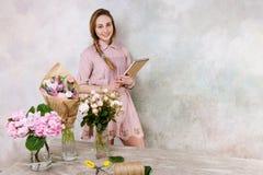 Florista de sorriso com lista de verificação na loja froristry fotografia de stock royalty free