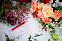 Florista del taller, tabla con las flores, aún vida Foco suave Foto de archivo