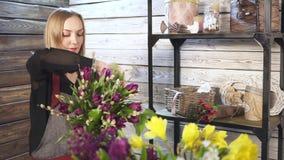 Florista em próprio florista, preparando ramalhetes filme