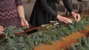 Florista en el trabajo: la mujer da la fabricación de la guirnalda de las decoraciones de la Navidad del abeto Nobilis Banquete d metrajes