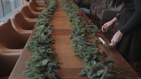 Florista en el trabajo: la mujer da la fabricación de la guirnalda de las decoraciones de la Navidad del abeto Nobilis Banquete d almacen de metraje de vídeo
