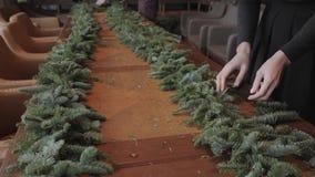 Florista en el trabajo: la mujer da la fabricación de la guirnalda de las decoraciones de la Navidad del abeto Nobilis Banquete d almacen de video