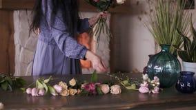 Florista en el trabajo: mujer adulta morena bonita que hace moda el ramo moderno de diversas flores y plantas en casa almacen de video