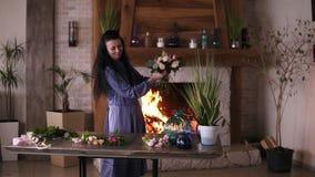 Florista en el trabajo: mujer adulta morena sonriente que hace moda el ramo moderno de diversas flores y plantas en casa almacen de video
