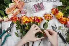 Florista en el trabajo Mujer que hace el ramo de la boda de rosas anaranjadas Fotografía de archivo libre de regalías