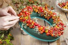 Florista en el trabajo: pasos de hacer la guirnalda de la puerta Imagen de archivo libre de regalías