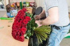 Florista en el trabajo que hace un ramo de rosas rojas foco en el bouq fotografía de archivo