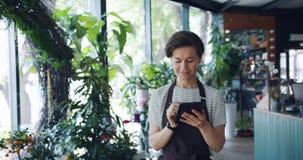 Florista fêmea bonito que conta as plantas que incorporam registros à tabuleta ocupada com trabalho vídeos de arquivo