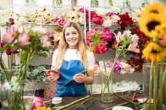 Florista fêmea que trabalha em um arranjo de flor fotografia de stock