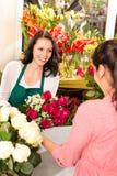 Florista feliz que hace rosas a mujeres del ramo cliente Imágenes de archivo libres de regalías