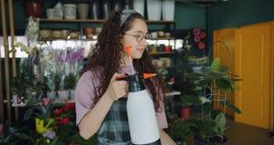 Florista joven sonriente que toma el cuidado de la planta verde que riega usando el rociador de la botella metrajes