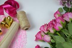Florista no trabalho: mulher bonita que faz o ramalhete do verão das rosas em uma tabela de funcionamento Papel de embalagem, tes Fotos de Stock Royalty Free