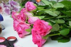 Florista no trabalho: mulher bonita que faz o ramalhete do verão das rosas em uma tabela de funcionamento Papel de embalagem, tes Imagens de Stock