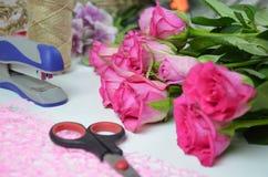 Florista no trabalho: mulher bonita que faz o ramalhete do verão das rosas em uma tabela de funcionamento Papel de embalagem, tes Fotos de Stock