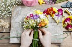 Florista no trabalho Mulher que faz o ramalhete de flores da frésia Fotos de Stock Royalty Free