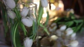 Florista no trabalho Tulipas brancas nos vasos de vidro claros, flores douradas na tabela video estoque