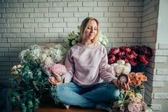 Florista precioso lindo de la mujer joven que se sienta en la posición de loto en floristería Fotografía de archivo libre de regalías