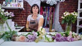Florista profissional que seleciona ramos cor-de-rosa para o arranjo do ramalhete da flor no estúdio do design floral filme