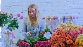 Florista profissional que trabalha com as flores no estúdio fotos de stock