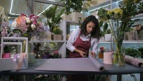 Florista que corta o papel de envolvimento para o ramalhete da flor filme