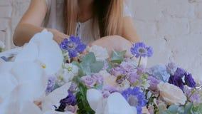 Florista que hace la cesta floral grande con las flores en la floristería almacen de video