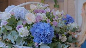 Florista que hace la cesta floral grande con las flores en la floristería metrajes
