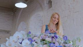 Florista que hace la cesta floral grande con las flores en la floristería almacen de metraje de vídeo