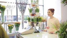 Florista que mostra flores à mulher no florista video estoque