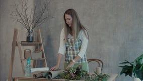 Florista que seleciona o papel de envolvimento para o ramalhete filme