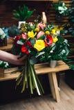 Florista que sostiene las flores hermosas del ramo imagenes de archivo
